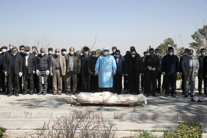 Mourners wearing face masks and gloves pray over the body of former politburo official in the Revolutionary Guard Farzad Tazari, who died Monday after being infected with the new coronavirus, at the Behesht-e-Zahra cemetery just outside Tehran, Iran, Tuesday, March 10, 2020. Iran is the hardest-hit country in the Mideast by the new coronavirus, which sickens but largely doesn't kill those afflicted. (Mahmood Hosseini/Tasnim News Agency via AP)