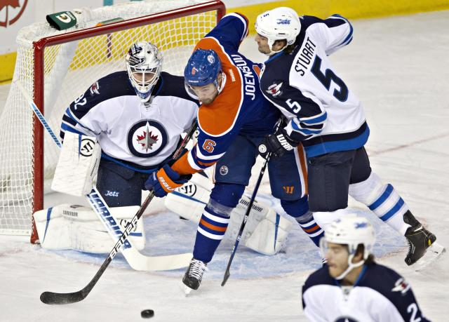 Winnipeg Jets goalie Edward Pasquale (32) watches as Mark Stuart (5) and Edmonton Oilers' Jesse Joensuu (6) look for a rebound during the first period of an NHL hockey preseason game Monday, Sept. 23, 2013, in Edmonton, Alberta.. (AP Photo/The Canadian Press, Jason Franson)