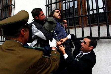 Police guards attempt to detain a chained demonstrator during a protest inside the government house against the government's education reform in Santiago, Chile, May 24, 2016. REUTERS/Stringer