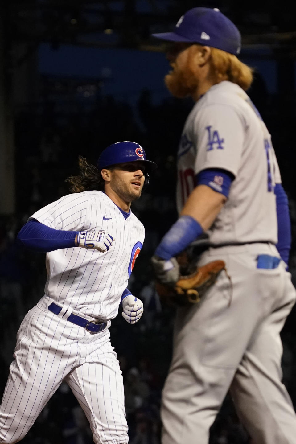 Chicago Cubs' Jake Marisnick, left, rounds the bases after his two-run home run as Los Angeles Dodgers third baseman Justin Turner looks at the score board during the fifth inning of a baseball game in Chicago, Wednesday, May 5, 2021. (AP Photo/Nam Y. Huh)