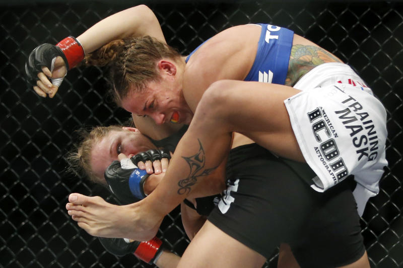 Liz Carmouche, top, grapples with Ronda Rousey during their UFC 157 women's bantamweight championship mixed martial arts match in Anaheim, Calif., Saturday, Feb. 23, 2013. Rousey won the first women's bout in UFC history, forcing Carmouche to tap out in the first round. (AP Photo/Jae C. Hong)
