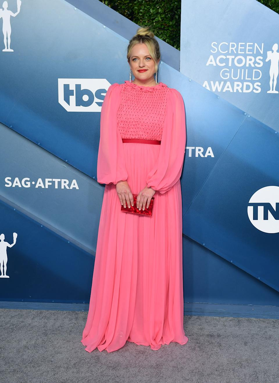 """<h2>Elisabeth Moss in Monique Lhuillier </h2><br>Elisabeth Moss follows Cynthia Erivo's lead in this red-and-pink long-sleeved frock designed by Monique Lhuillier. <span class=""""copyright"""">Photo by FREDERIC J. BROWN/AFP via Getty Images.</span>"""