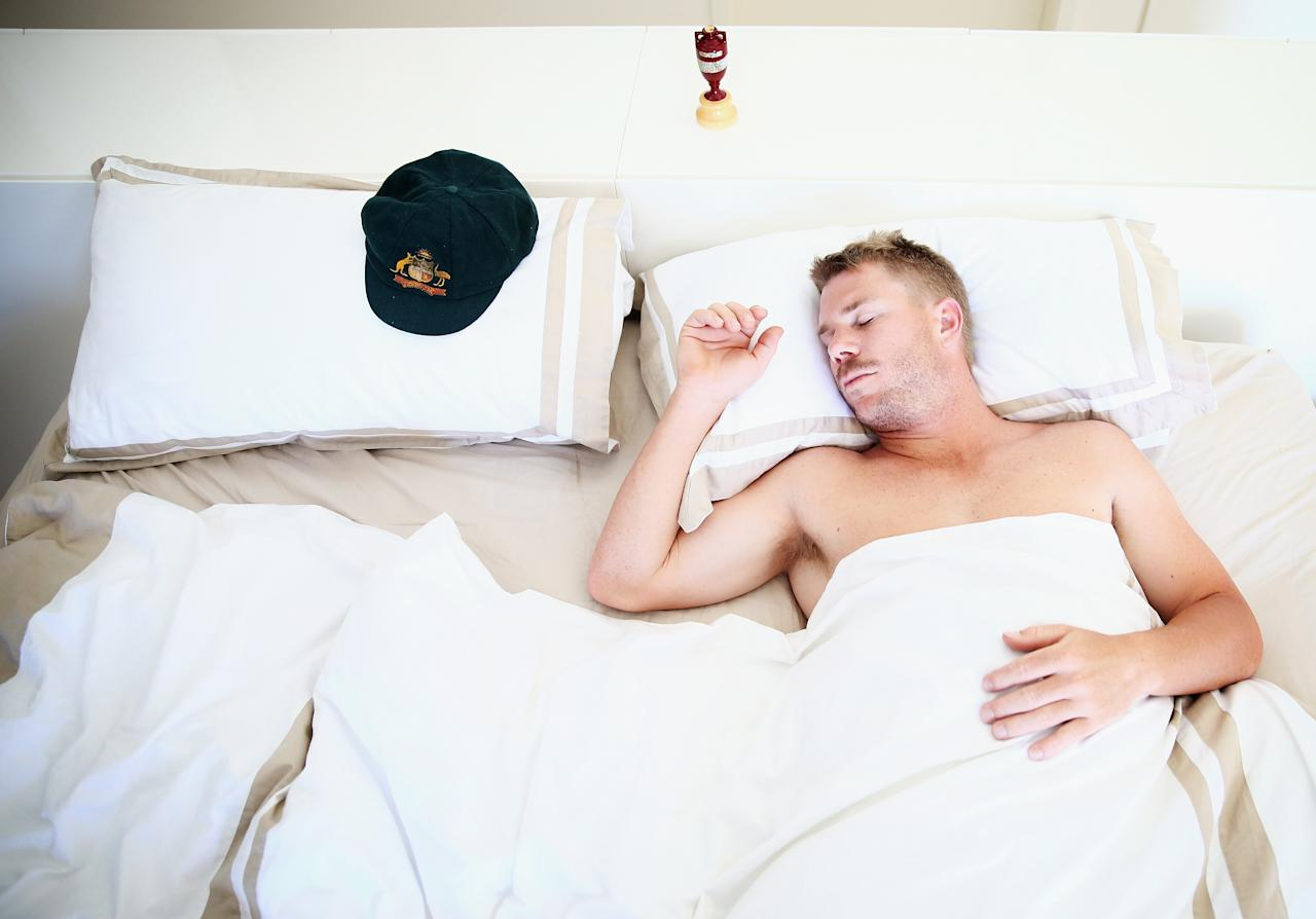 SYDNEY, AUSTRALIA - JANUARY 06:  Australian Cricketer David Warner sleeps next to his Baggy Green Cap and a replica Ashes Urn at his home on January 6, 2014 in Sydney, Australia. Australia yesterday claimed a five-nil Ashes series victory over England in which Warner was leading run scorer.  (Photo by Ryan Pierse/Getty Images)