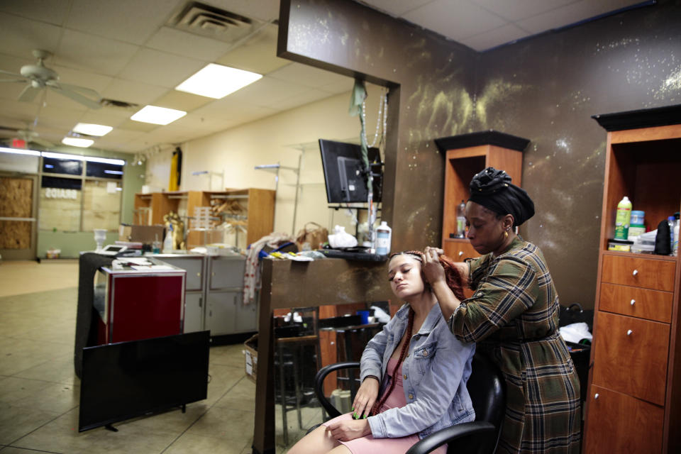 Matilda Kromah, right, braids a clients hair at her salon, Thursday, April 22, 2021, in Brooklyn Center, Minn. The salon was looted after a white police officer fatally shot a Black man this month, and Kromah faced a resurgence of the trauma from the civil war in Liberia she fled over 20 years ago. (AP Photo/Stephen Groves)