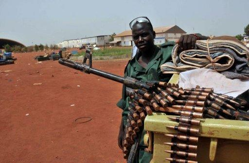 """A Sudanese soldier poses next to a machine gun in the oil region of Heglig. Khartoum's warplanes bombed border regions, leading South Sudan's leader on Tuesday to accuse Sudan of declaring war, as the United States condemned the """"provocative"""" strikes"""