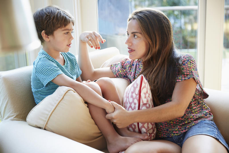 Mother talking to son on the sofa about coronavirus