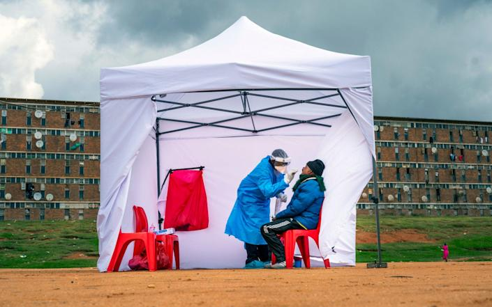 A resident from the Alexandra township gets tested for COVID-19 in Johannesburg, South Africa. A dangerous stigma has sprung up around the coronavirus in Africa fueled, in part, by severe quarantine rules in some countries as well as insufficient information about the virus. - Jerome Delay/AP