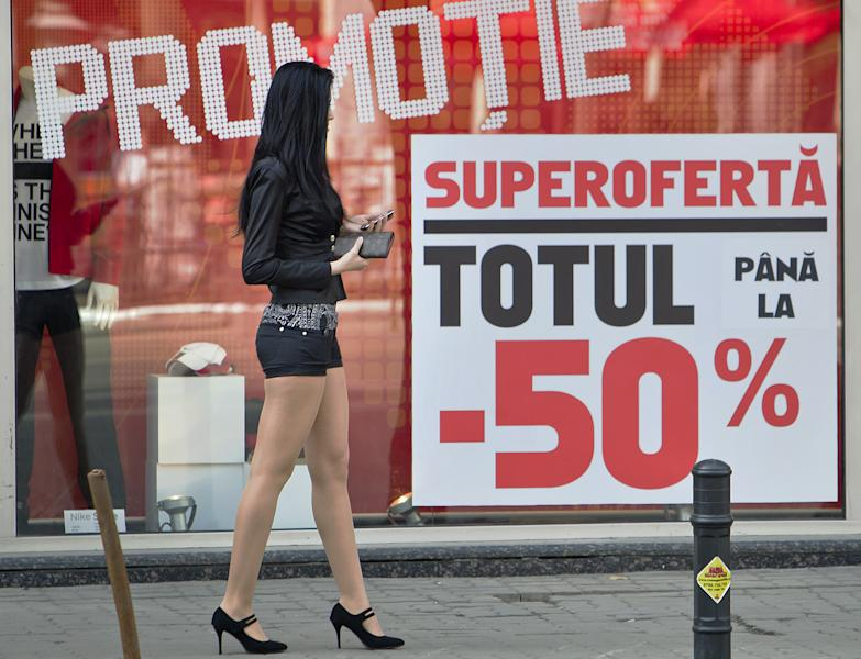 A girl walks downtown Bucharest, Romania, back dropped by a shop window advertising price reductions for sports equipment, Monday, March 19, 2012. The coldest winter in living memory is over, and spring has arrived in Prague, Belgrade and Bucharest, but from the look in shop windows, with massive reductions and bargains galore, you'd think we were still in the winter sales.(AP Photo/Vadim Ghirda)