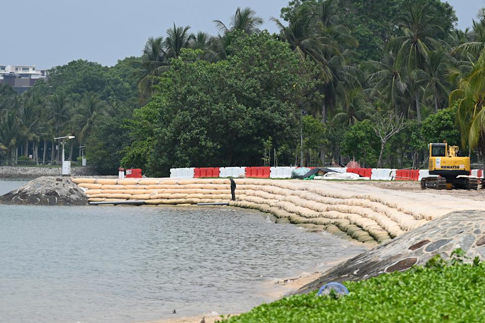 A worker stands on sandbags, laid along the shore to prevent erosion during high-tide periods, at a beach in Singapore on April 13, 2021. (PHOTO: AFP via Getty Images)