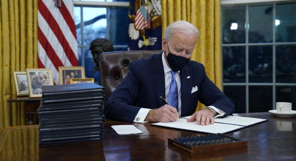 "<span class=""caption"">U.S. President Joe Biden signs his first executive order in the Oval Office of the White House on Jan. 20, 2021, in Washington. </span> <span class=""attribution""><span class=""source"">(AP Photo/Evan Vucci)</span></span>"