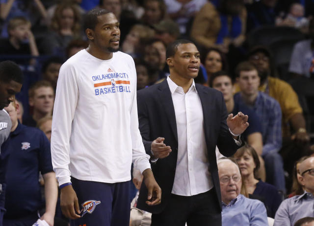Oklahoma City Thunder forward Kevin Durant, left, and guard Russell Westbrook right, watch from the bench in the fourth quarter of an NBA basketball game against the Sacramento Kings in Oklahoma City, Sunday, Jan. 19, 2014. Oklahoma City won 108-93. (AP Photo/Sue Ogrocki)