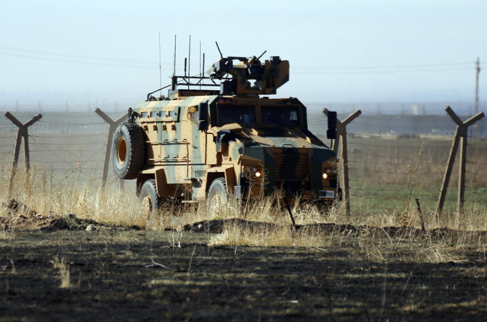 In this photo taken from the outskirts of the village of Alakamis, in Idil province, southeastern Turkey, a Turkish army vehicles is driven in Turkey after conducting a joint patrol with Russian forces in Syria, Friday, Nov. 8, 2019. The Britain-based Syrian Observatory for Human Rights says a protester has been killed when he was run over in the village of Sarmasakh, Syria near the border by a Turkish vehicle during a joint patrol with Russia.The man was among residents who pelted with shoes and stones Turkish and Russian troops who were conducting their third joint patrol in northeastern Syria, under a cease-fire deal brokered by Moscow that forced Kurdish fighters to withdraw from areas bordering Turkey. (AP Photo/Mehmet Guzel)