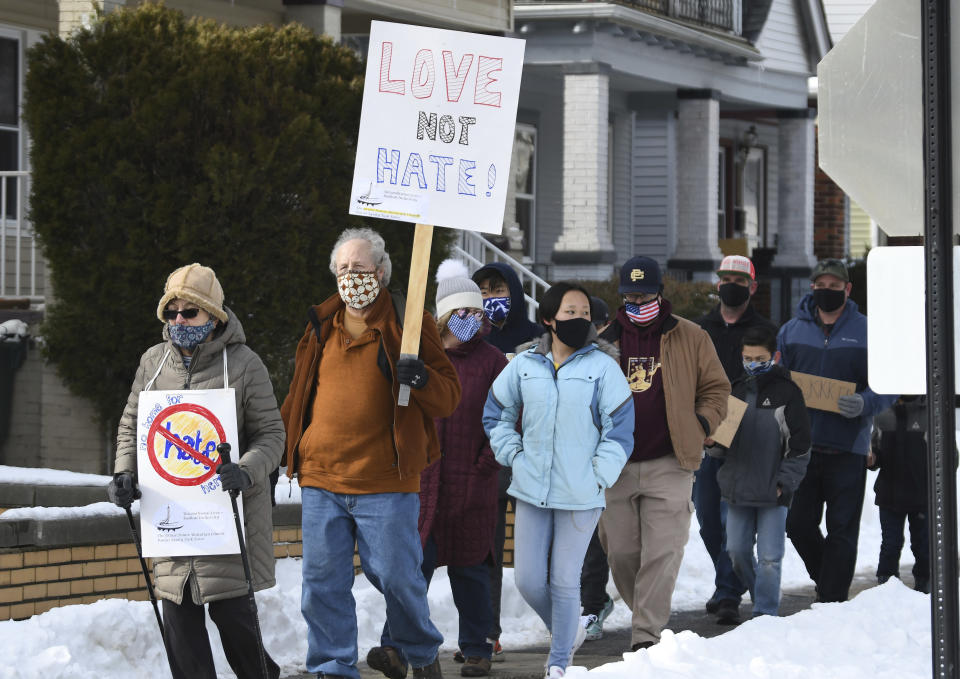 Chuck Palmer, 67, second from left, of Grosse Pointe Parks, walks south on Wayburn St. during the walking rally to protest hate and racism, Sunday, Feb. 21, 2021 in Grosse Pointe Park, Mich., following a white resident's display of a Ku Klux Klan flag in a side window facing their Black neighbor's home. JeDonna Dinges, 57, of Grosse Pointe Park, said the klan flag was hanging next door in a window directly across from her dining room. The incident occurred two weeks ago. (Clarence Tabb, Jr./Detroit News via AP)
