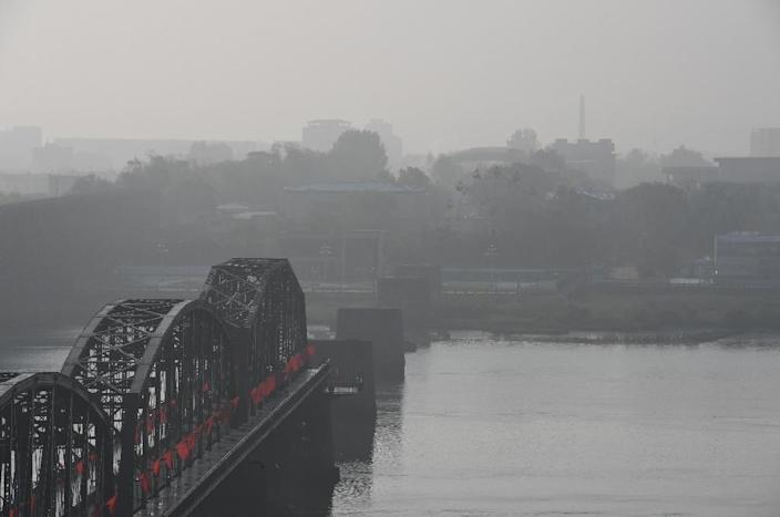Buildings are seen through fog in the North Korean town of Sinuiju, behind the Broken Bridge, from Dandong in north-east China, on September 11, 2016 (AFP Photo/Greg Baker)