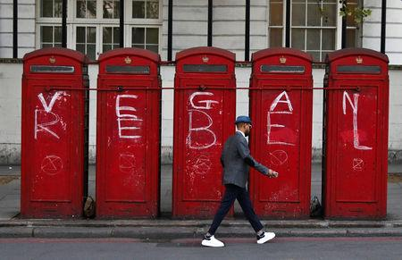A man walks past phone boxes at Marble Arch during the Extinction Rebellion protest in London, Britain April 20, 2019. REUTERS/Kevin Coombs