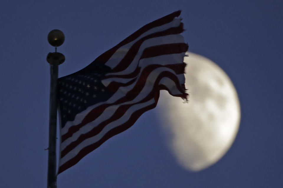 A flag flies in the wind above City Hall as the waxing gibbous moon passes behind clouds overhead Monday, June 29, 2020, in Kansas City, Mo. (AP Photo/Charlie Riedel)