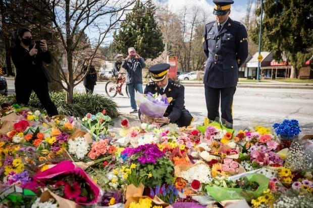 RCMP Supt. Ghalib Bhayani lays flowers at a memorial outside the Lynn Valley Library.
