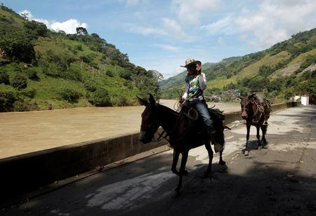 A man rides his horse along the river at the municipal coliseum after the Colombian government ordered the evacuation of residents living along the Cauca river, as construction problems at a hydroelectric dam prompted fears of massive flooding, in Valdivia, Colombia May 18, 2018. REUTERS/Fredy Builes