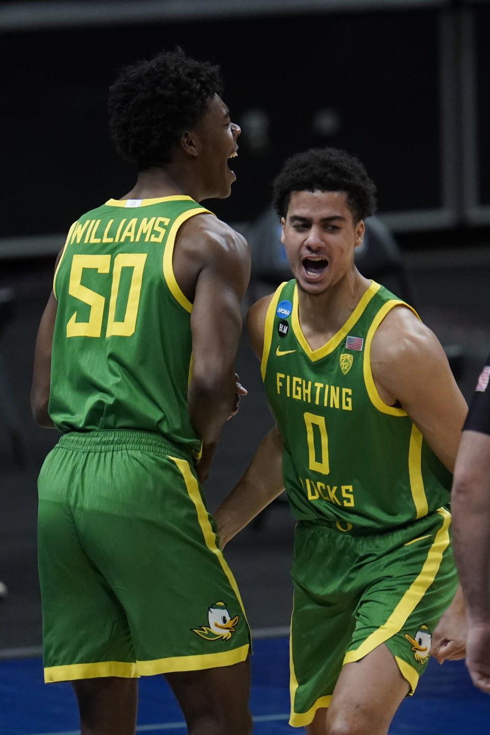 Oregon forward Eric Williams Jr. (50) and Will Richardson (0) celebrate a basket during the first half of a men's college basketball game in the second round of the NCAA tournament at Bankers Life Fieldhouse in Indianapolis, Monday, March 22, 2021. (AP Photo/Paul Sancya)
