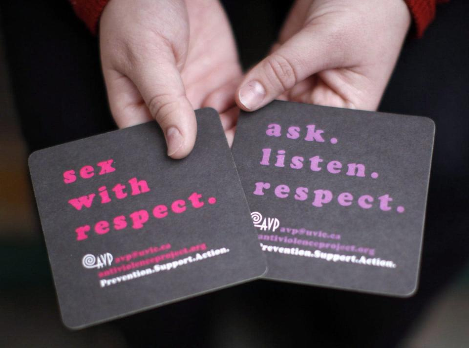 """<span class=""""caption"""">In this 2016 photo, a University of Victoria student holds coasters with messages about consensual sex.</span> <span class=""""attribution""""><span class=""""source"""">THE CANADIAN PRESS/Chad Hipolito</span></span>"""