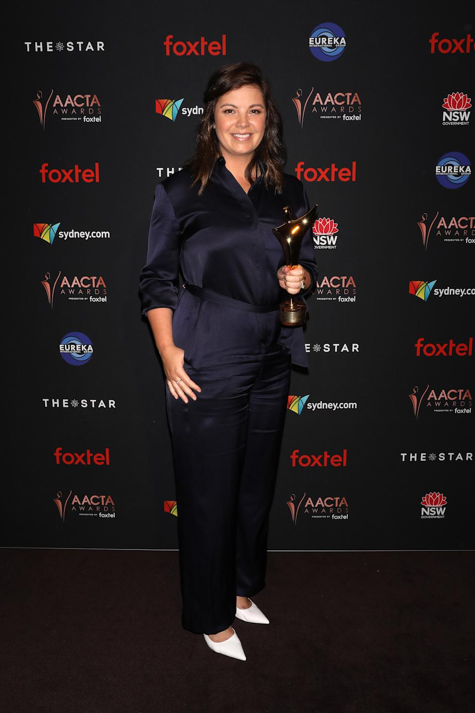 Yvonne Sampson poses and smiles with the AACTA Award for Best Female Presenter in the media room.