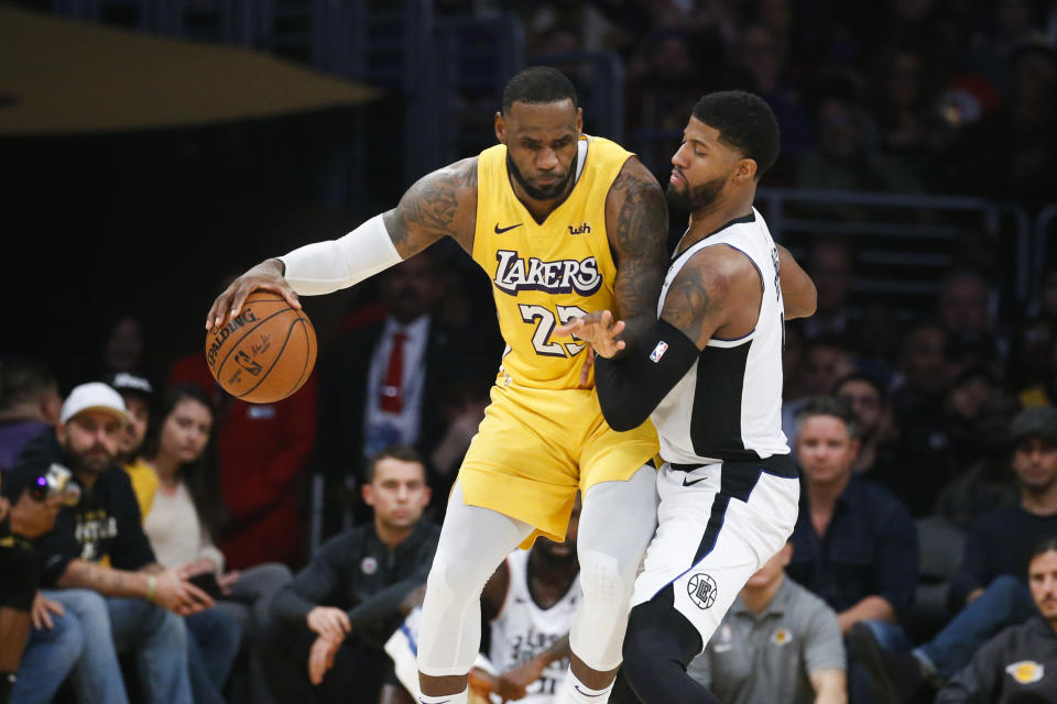 Los Angeles Lakers' LeBron James (23) is defended by Los Angeles Clippers' Paul George (13) during an NBA basketball game between Los Angeles Lakers and Los Angeles Clippers, Wednesday, Dec. 25, 2019, in Los Angeles. The Clippers won 111-106. (AP Photo/Ringo H.W. Chiu)