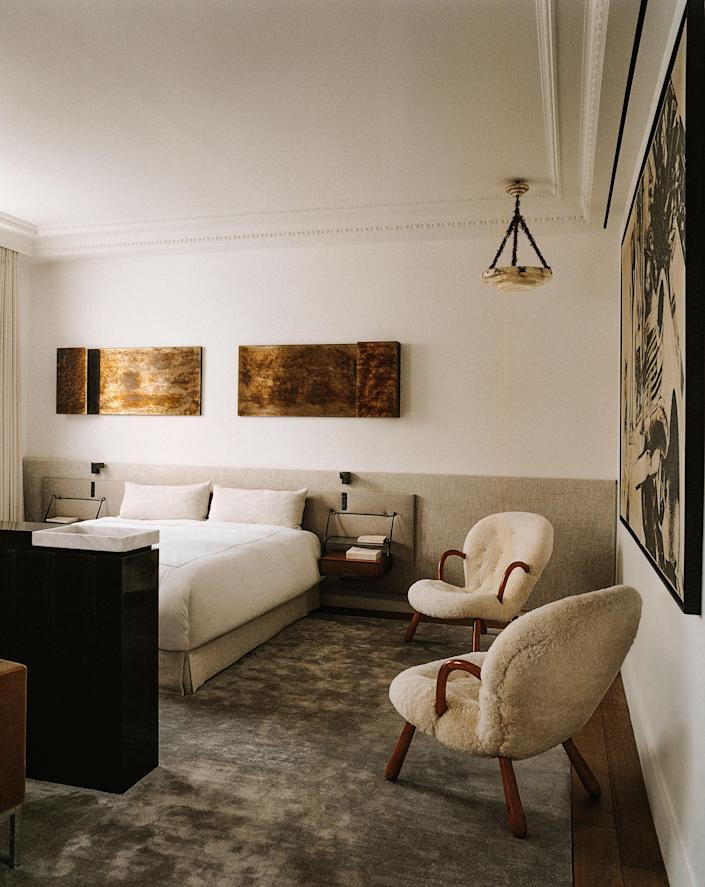In the primary bedroom a vintage alabaster ceiling light from Milan's Nilufar gallery floats above a pair of Philip Arctander armchairs. Above bed, wall lamps by Dimorestudio; vintage bedside tables by Silvio Cavatorta; reading lamps by Ozone from the Invisible collection.