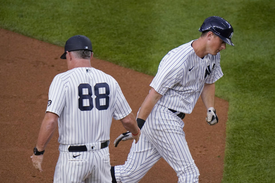 New York Yankees' DJ LeMahieu celebrates with third base coach Phil Nevin, left, as he runs the bases after hitting a two-run home run during the third inning of the team's baseball game against the Oakland Athletics on Friday, June 18, 2021, in New York. (AP Photo/Frank Franklin II)