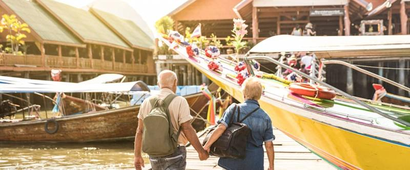 Happy senior couple walking holding hand at Koh Panyi muslim floating village - Active elderly and travel lifestyle concept with retired mature people at Phang Nga bay Thailand