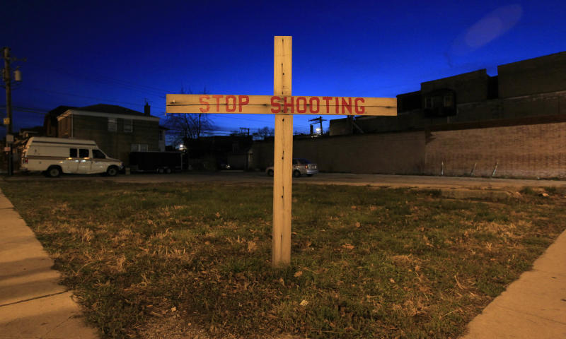 In this Wednesday, Dec. 5, 2012 photo, a lone cross stands in a vacant lot on the corner of 79th and Loomis in the Auburn-Gresham neighborhood on Chicago's South Side. Up to 80 percent of Chicago's murders and shootings are gang-related, according to police. By one estimate, the city has almost 70,000 gang members. A police audit last spring identified 59 gangs and 625 factions; most are on the South and West sides. (AP Photo/Charles Rex Arbogast)