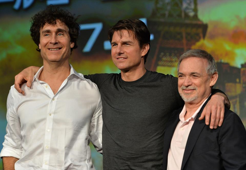 """US actor Tom Cruise (C), accompanied by film director Doug Liman (L) and producer Erwin Stoff (R) pose at a press conference for their latest movie """"Edge of Tomorrow"""" in Tokyo on June 27, 2014. The three are here to promote the science fiction film, adapted from the novel """"All You Need Is Kill"""" written by Japanese novelist Hiroshi Sakurazaka.    AFP PHOTO / Yoshikazu TSUNO        (Photo credit should read YOSHIKAZU TSUNO/AFP via Getty Images)"""