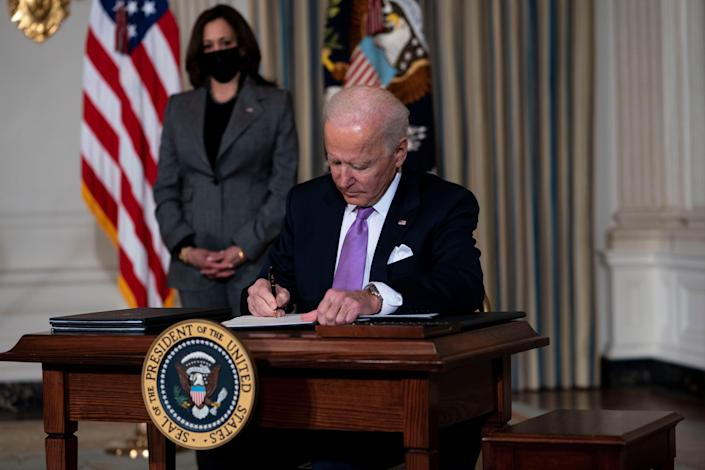 Vice President Kamala Harris looks on as President Joe Biden signs executives orders related to his racial equity agenda in the State Dining Room of the White House on Jan. 26, 2021.