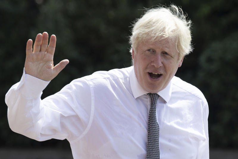 Britain's Prime Minister Boris Johnson waves as he walks to his car following a visit to Hereford County Hospital, in Hereford, England, Tuesday, Aug. 11, 2020. Hereford County Hospital is expanding with a three storey modular building providing 72 new beds over three wards under construction. The new facility will open early 2021. (Matthew Horwood/Pool Photo via AP)