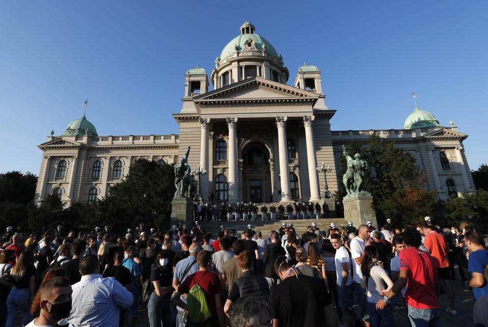 People gather in front of the Serbian Parliament building, heavily guarded by riot police, during a demonstration in Belgrade, Serbia, Wednesday, July 8, 2020. Serbia's president Aleksandar Vucic backtracked Wednesday on his plans to reinstate a coronavirus lockdown in Belgrade after thousands protested the move and violently clashed with the police in the capital. (AP Photo/Darko Vojinovic)