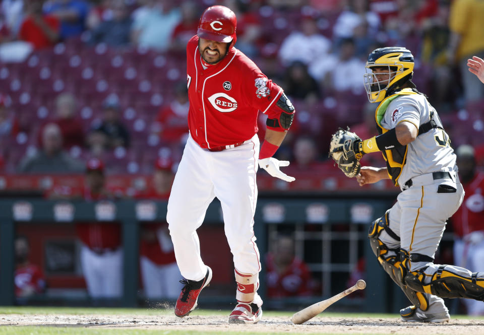 Cincinnati Reds' Eugenio Suarez, left, reacts after being hit by a pitch by Pittsburgh Pirates relief pitcher Clay Holmes during the ninth inning of a baseball game, Wednesday, May 29, 2019, in Cincinnati. At right is Pirates catcher Elias Diaz. The Pirates won 7-2. (AP Photo/Gary Landers)