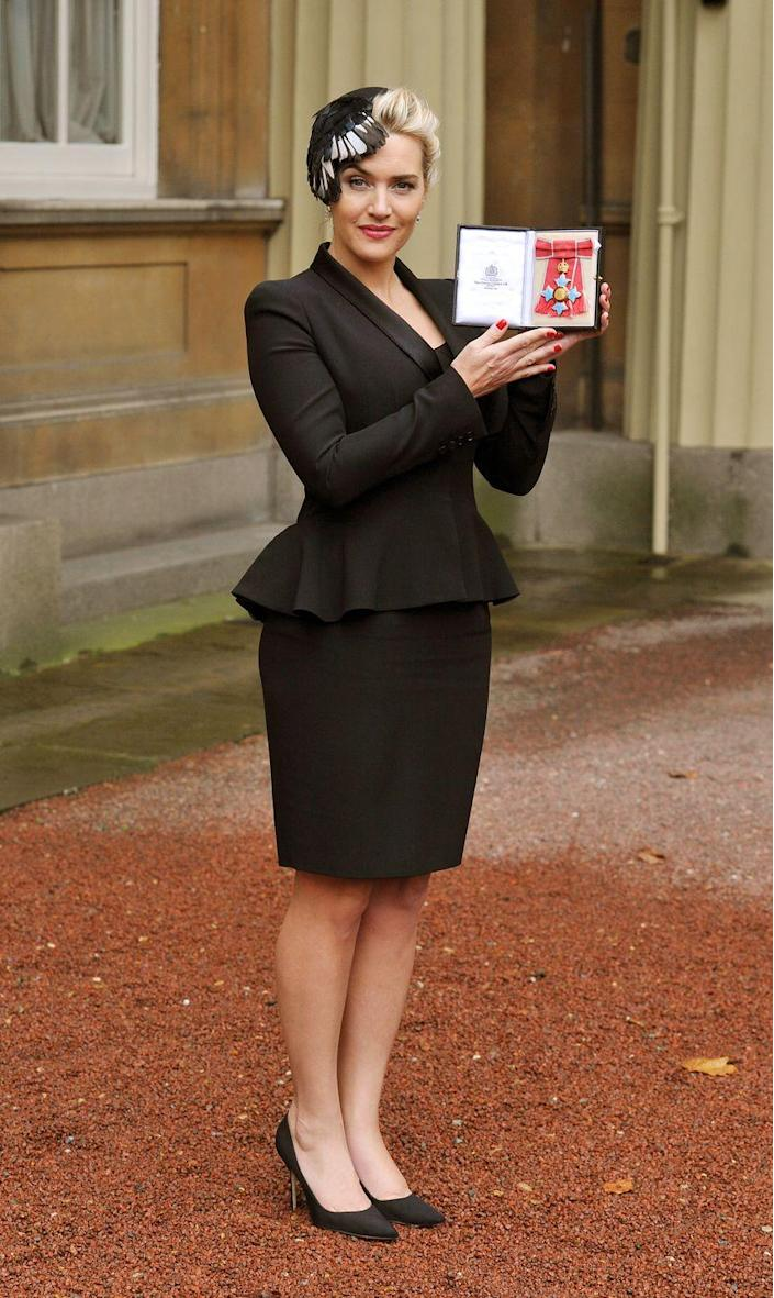 <p>Kate Winslet oozed British class and aristocracy in a feathered fascinator and black peplum suit jacket after receiving her OBE from the Queen at Buckingham Palace. </p>