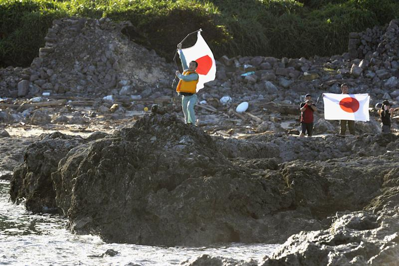 Japanese activists hold the national flags on Uotsuri island, one of the islands of Senkaku in Japanese and Diaoyu in Chinese, in East China Sea, Sunday, Aug. 19, 2012. Japan's Coast Guard says a group of Japanese activists have landed on Uotsuri island, one of a group of islands at the center of an escalating territorial dispute with China. (AP Photo/Kyodo News) JAPAN OUT, MANDATORY CREDIT, NO LICENSING IN CHINA, HONG KONG, JAPAN, SOUTH KOREA AND FRANCE
