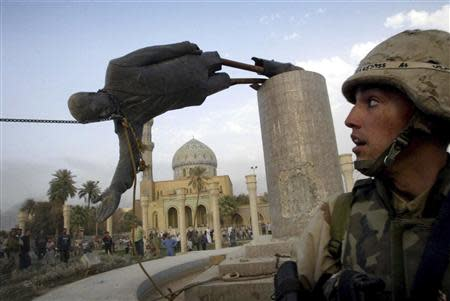 U.S. Marine Corp Assaultman Kirk Dalrymple watches as a statue of Iraq's President Saddam Hussein falls in central Baghdad's Firdaus Square, in this file photo from April 9, 2003. REUTERS/Goran Tomasevic/Files