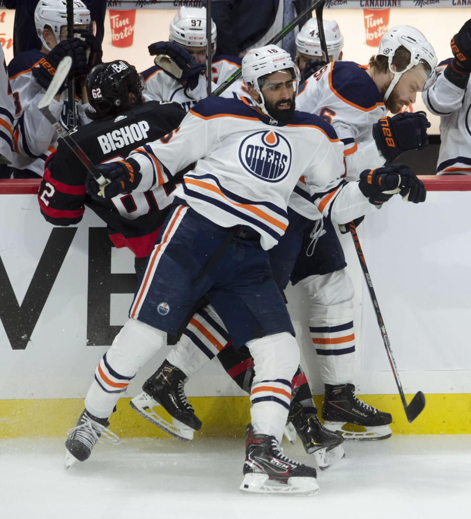 Edmonton Oilers defenseman Adam Larsson, right, and left wing Jujhar Khaira get the upper hand on Ottawa Senators' Clark Bishop along the boards during the third period of an NHL hockey game Wednesday, April 7, 2021, in Ottawa, Ontario. (Adrian Wyld/The Canadian Press via AP)