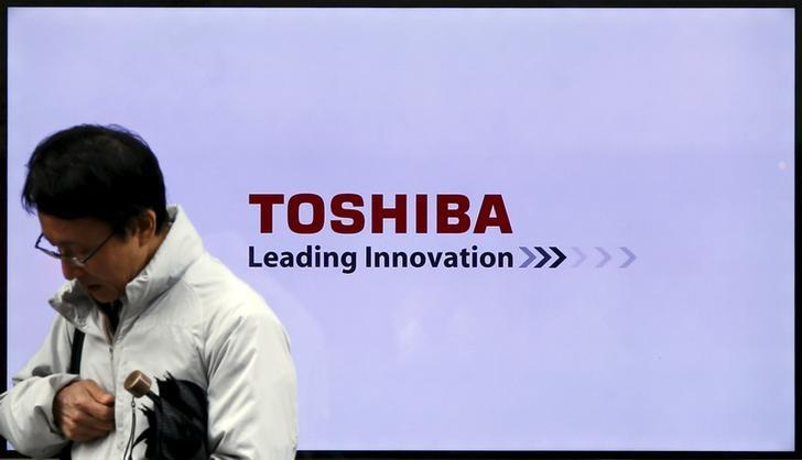 A man walks past a Toshiba Corp logo displayed on one of its television sets in Tokyo, Japan
