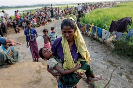 A Rohingya refugee woman who crossed the border from Myanmar a day before, carries her daughter and searches for help as they wait to receive permission from the Bangladeshi army to continue their way to the refugee camps, in Palang Khali, Bangladesh October 17, 2017. REUTERS/Jorge Silva