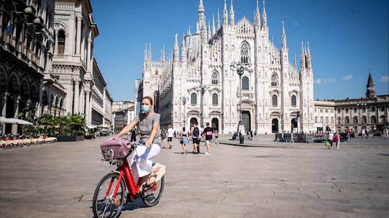 A woman is seen riding her bike in Milan, Italy, while wearing a mask.