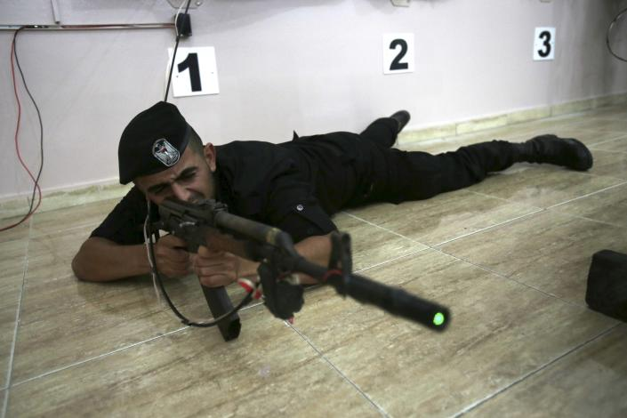 Palestinian security officer Muhmmad Debo, 22, fires an electronically-modified AK-47 rifle at the headquarters of the security training department of the Hamas interior ministry in Gaza City, in the northern Gaza Strip on Thursday, April 10, 2014. The laser-fitted rifles are a money saver that eliminates the need to train with live ammunition, which is in short supply in Gaza. (AP Photo/Adel Hana)