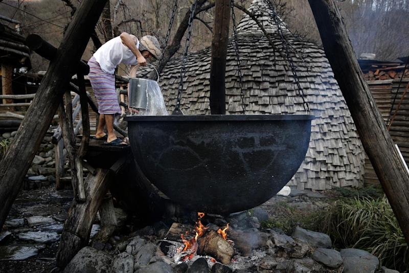 Bathhouse worker Alexander Bogatov prepares a hot pot at the British Banya bathhouse, Saturday, Feb. 15, 2014, in Krasnaya Polyana, Russia. Preparations begin late in the afternoon, at least three hours before the bathing party arrives. (AP Photo/Jae C. Hong)