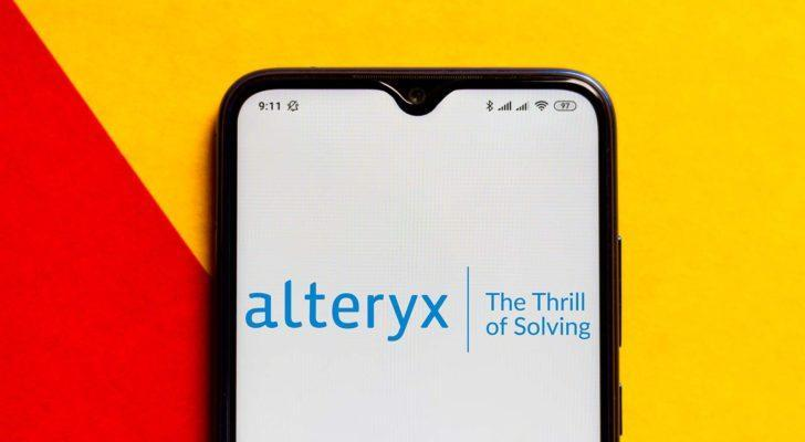 The Alteryx (AYX) logo is displayed on a smartphone screen.