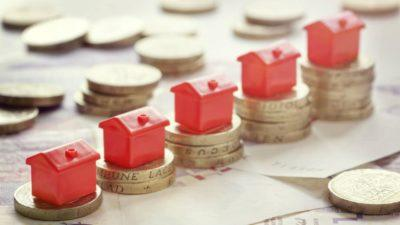 Models of houses on top of pound coins