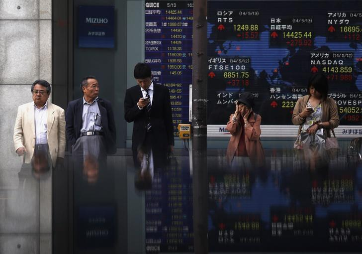 Pedestrians standing in front of an electronic board showing the various countries' stock market indices outside a brokerage are reflected in a polished stone surface, in Tokyo