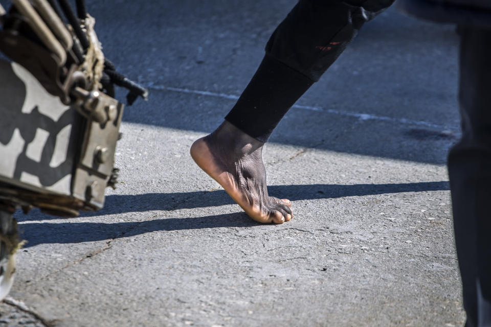 A migrant steps on the ground barefoot in the Sicilian port of Empedocle, Italy after being rescued by the Spanish NGO Open Arms in the the Mediterranean Sea, Tuesday, Feb 16, 2021. Various African migrants drifting in the Mediterranean Sea after fleeing Libya on unseaworthy boats have been rescued. In recent days, the Libyans had already thwarted eight rescue attempts by the Open Arms, a Spanish NGO vessel, harassing and threatening its crew in international waters. (AP Photo/Bruno Thevenin)