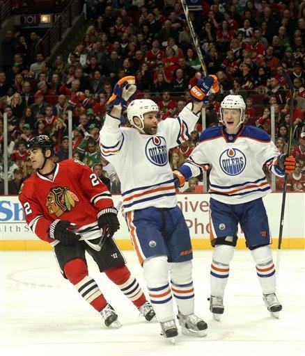 Edmonton Oilers' Mike Brown, center, celebrates his goal with teammate Lennart Petrell (37), from Finland, as Chicago Blackhawks center Jamal Mayers skates away during the first period of an NHL hockey game Sunday, March 10, 2013 in Chicago. (AP Photo/Charles Rex Arbogast)