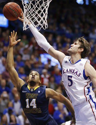 Kansas center Jeff Withey (5) blocks a shot by West Virginia guard Gary Browne (14) during the second half of an NCAA college basketball game in Lawrence, Kan., Saturday, March 2, 2013. Kansas defeated West Virginia 91-65. (AP Photo/Orlin Wagner)